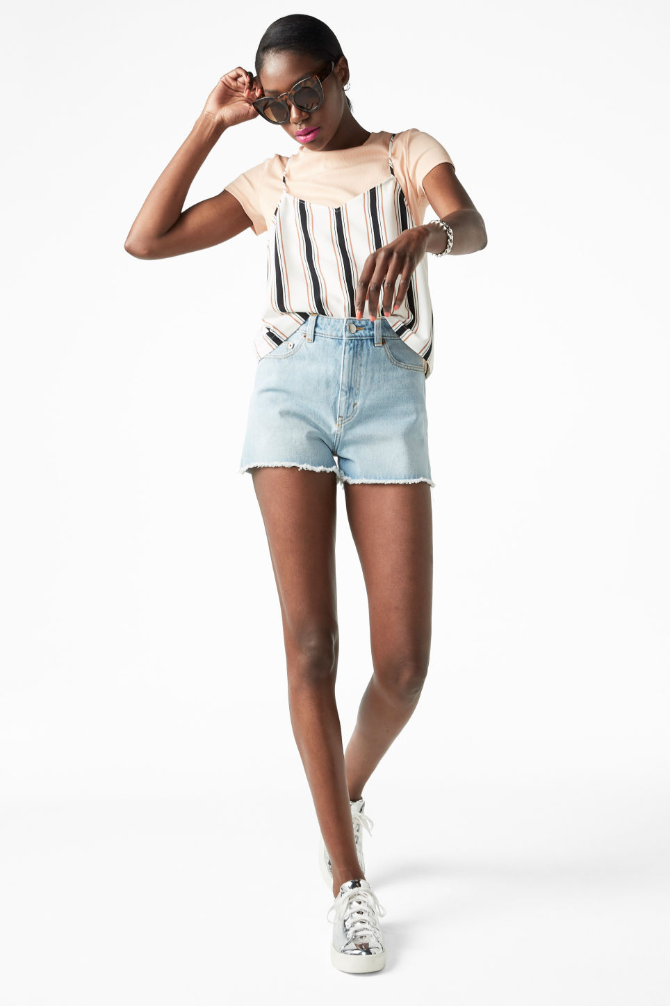 Model side image of Monki high waist denim shorts in blue