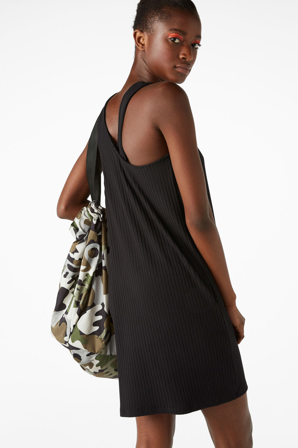 Model side image of Monki sleeveless dress with cross back in black