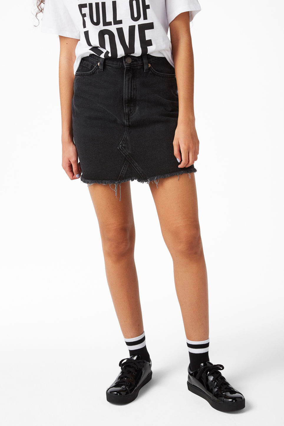 Model side image of Monki frayed hem denim skirt in black