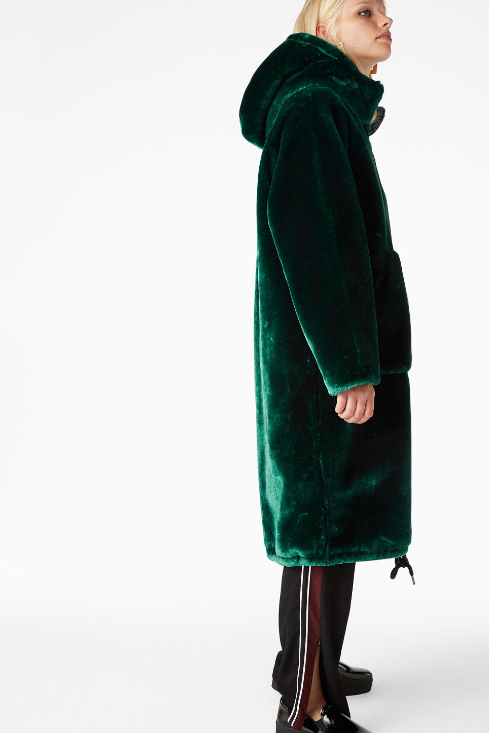 Model side image of Monki hooded faux fur coat in green