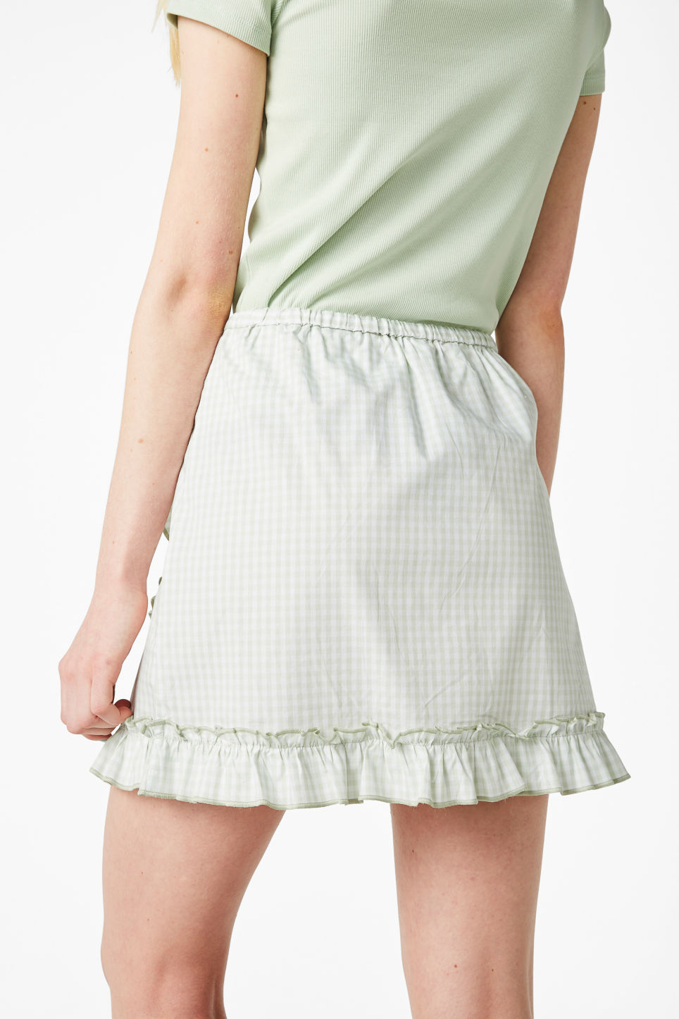 Model side image of Monki ruffle wrap skirt in green