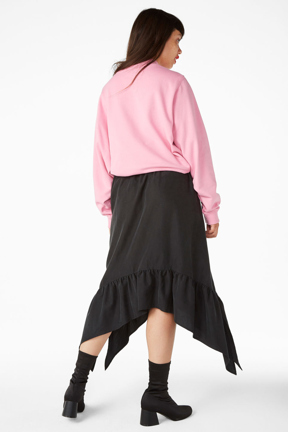 Model side image of Monki asymmetrical ruffle skirt in black