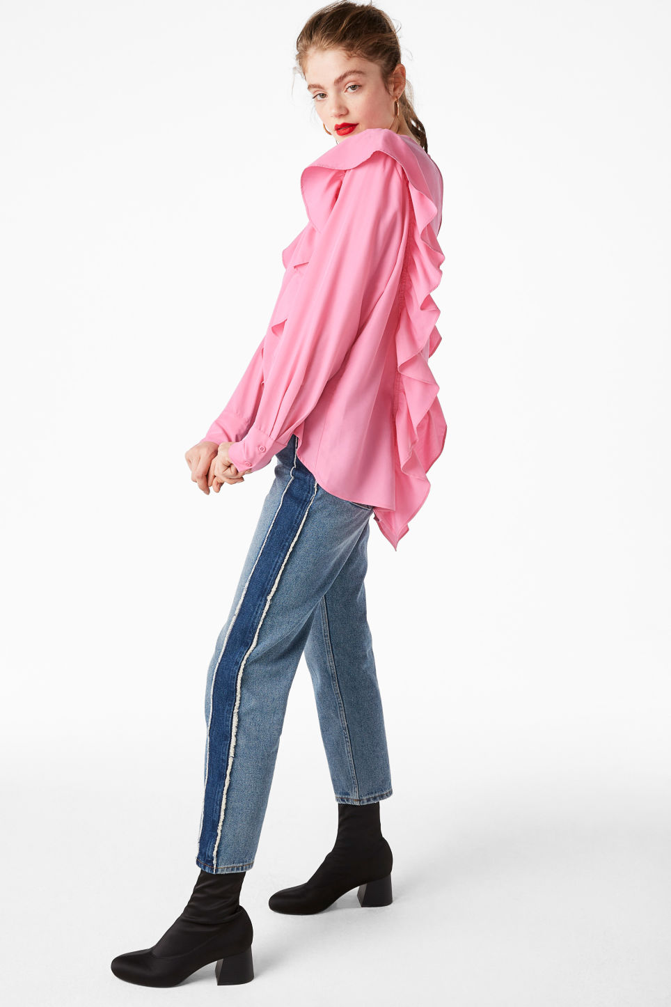 Model side image of Monki ruffled mullet hem blouse in pink