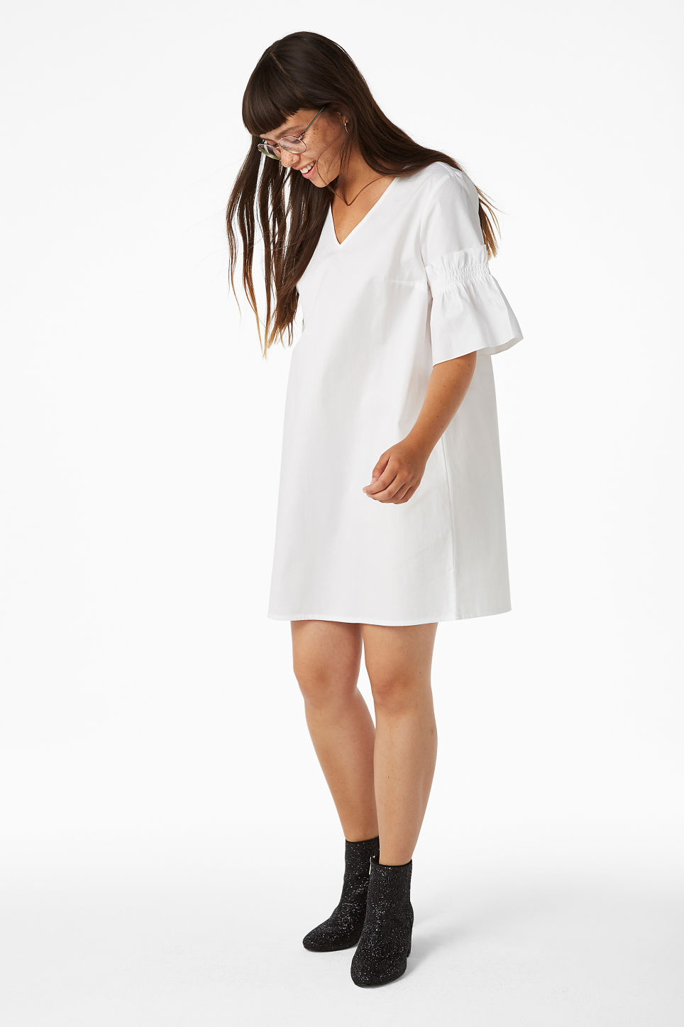 Model side image of Monki ruffled sleeve dress in white