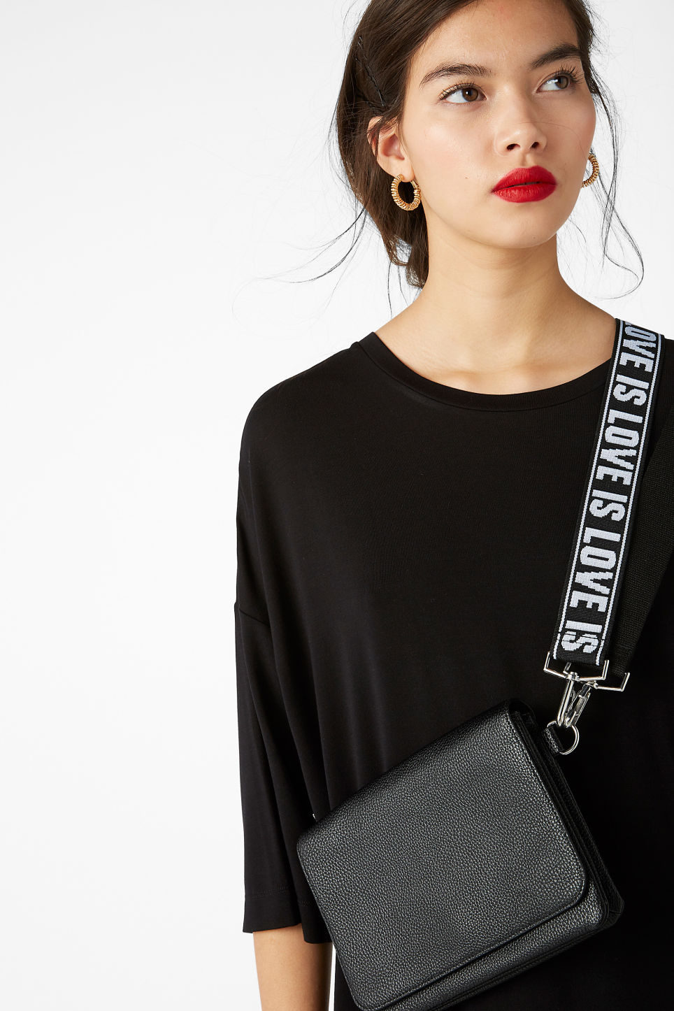 Model side image of Monki statement bag in black