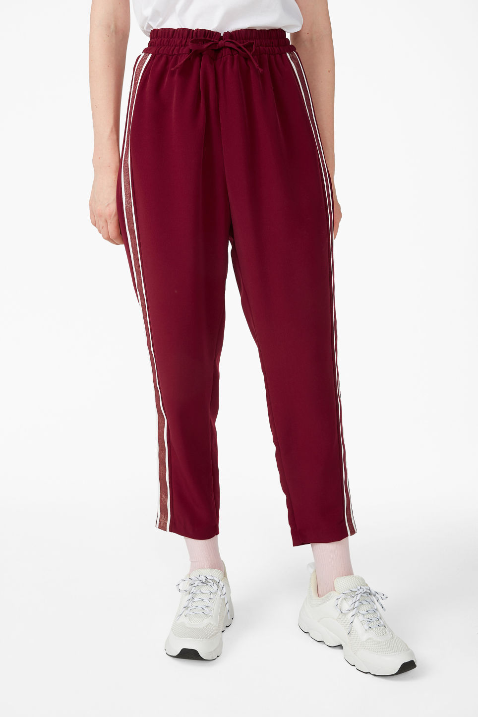 Model side image of Monki side stripe trousers in red