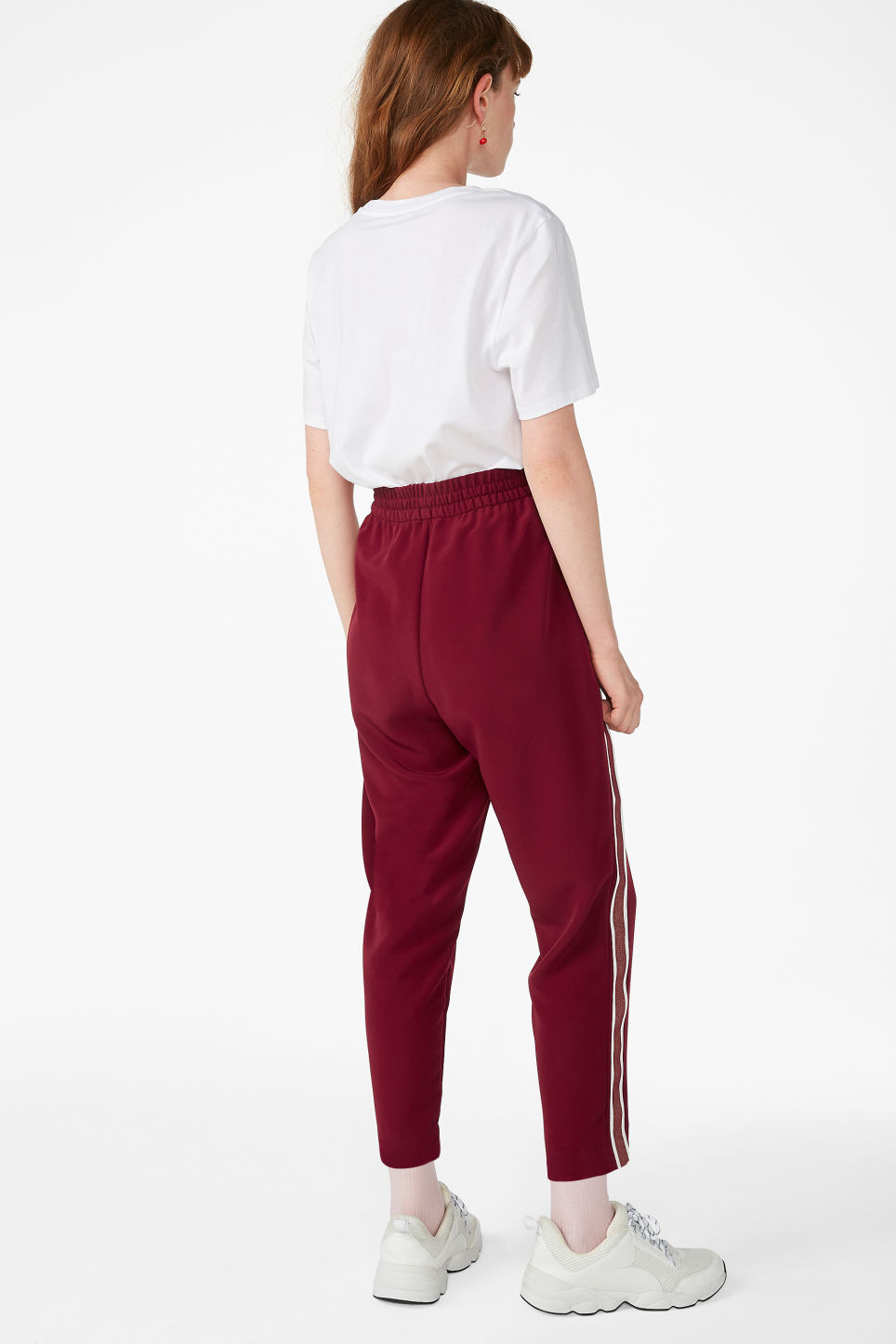 Model back image of Monki side stripe trousers in red
