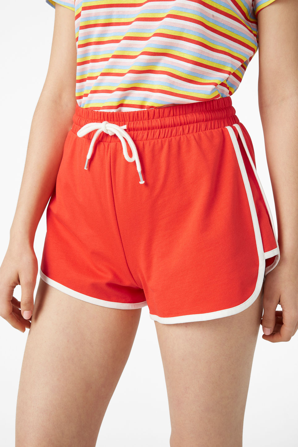 Model side image of Monki sporty shorts in red