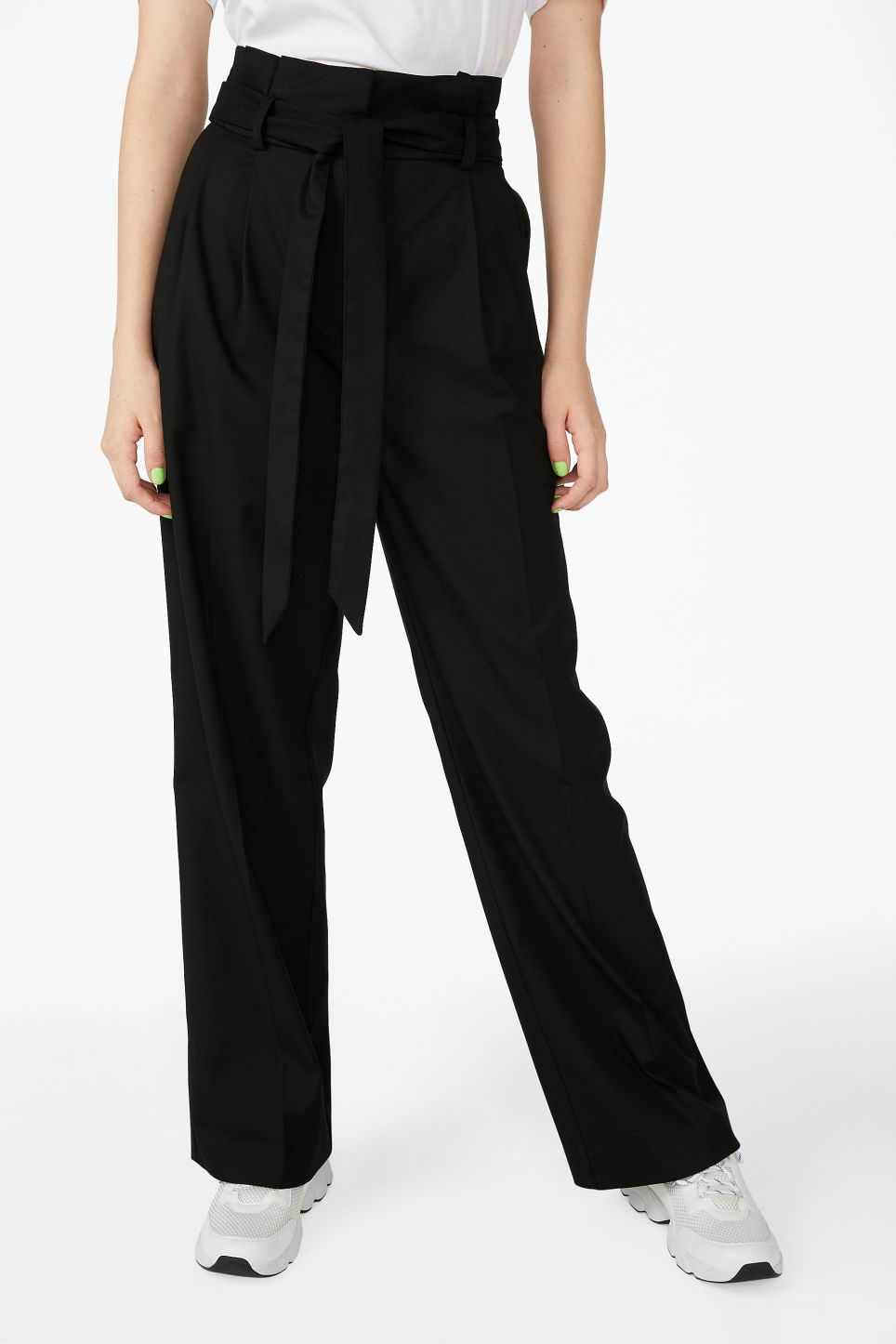 Model side image of Monki smart trousers with tie detail in black