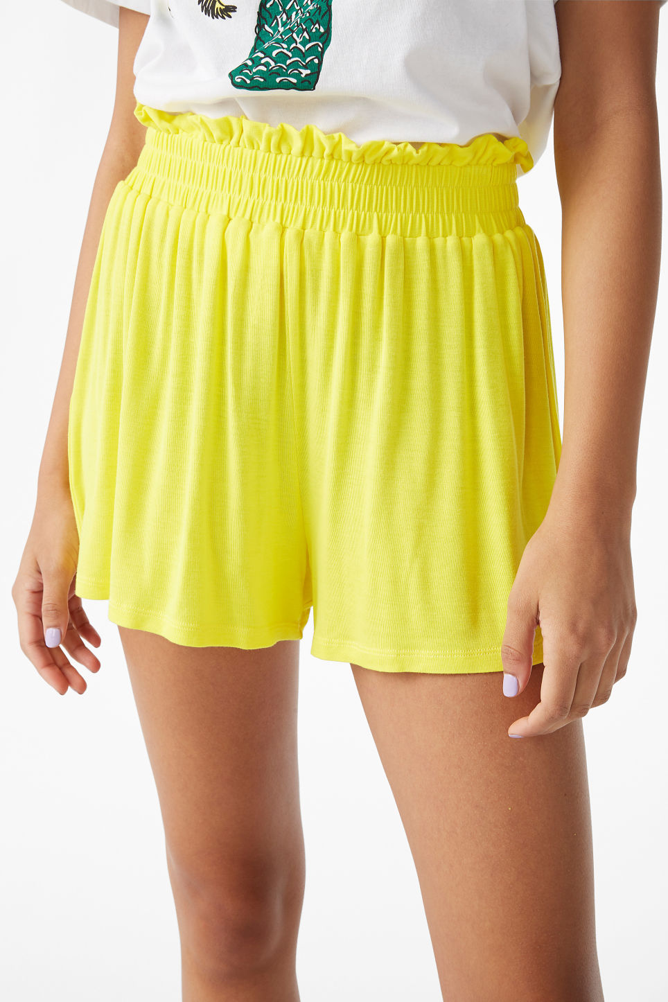 Model side image of Monki soft shorts in yellow