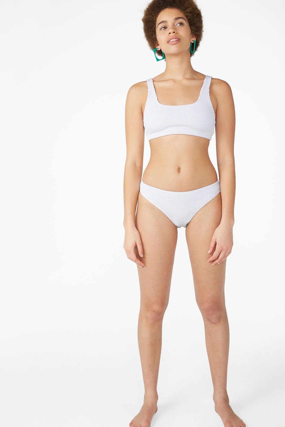 Model side image of Monki shirred bikini top in white
