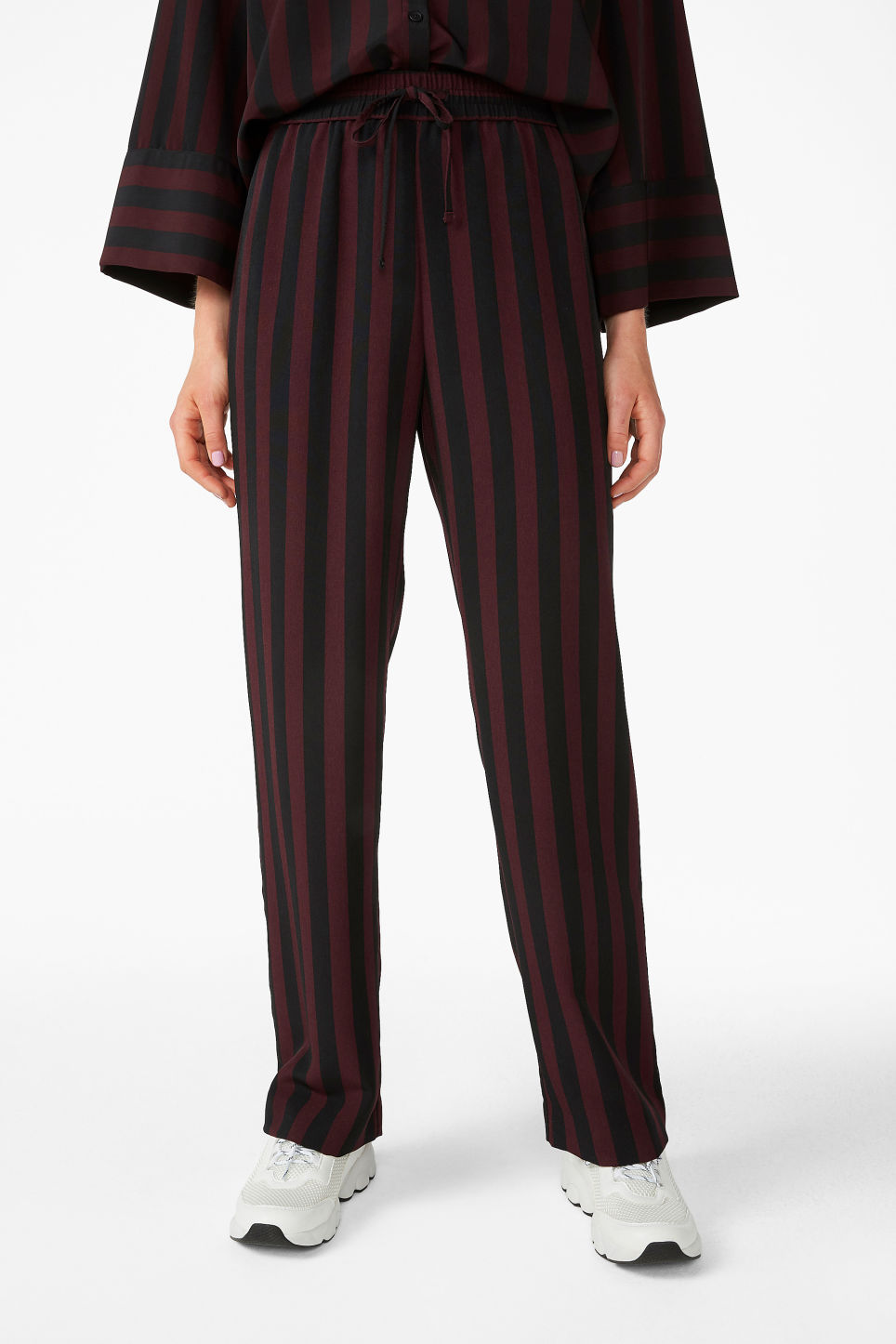 Model side image of Monki dressy trousers in red