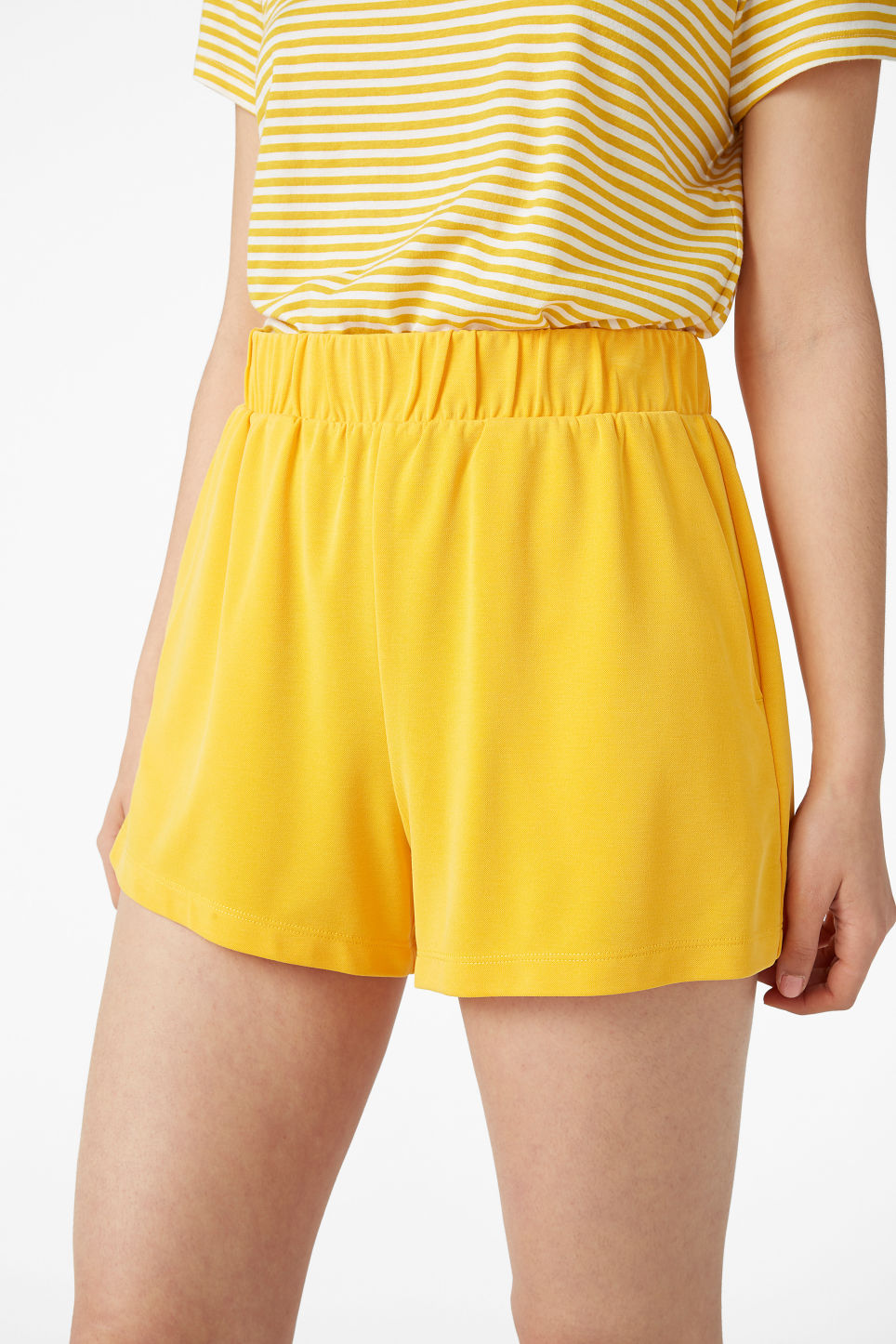 Model side image of Monki super-soft sporty shorts in yellow