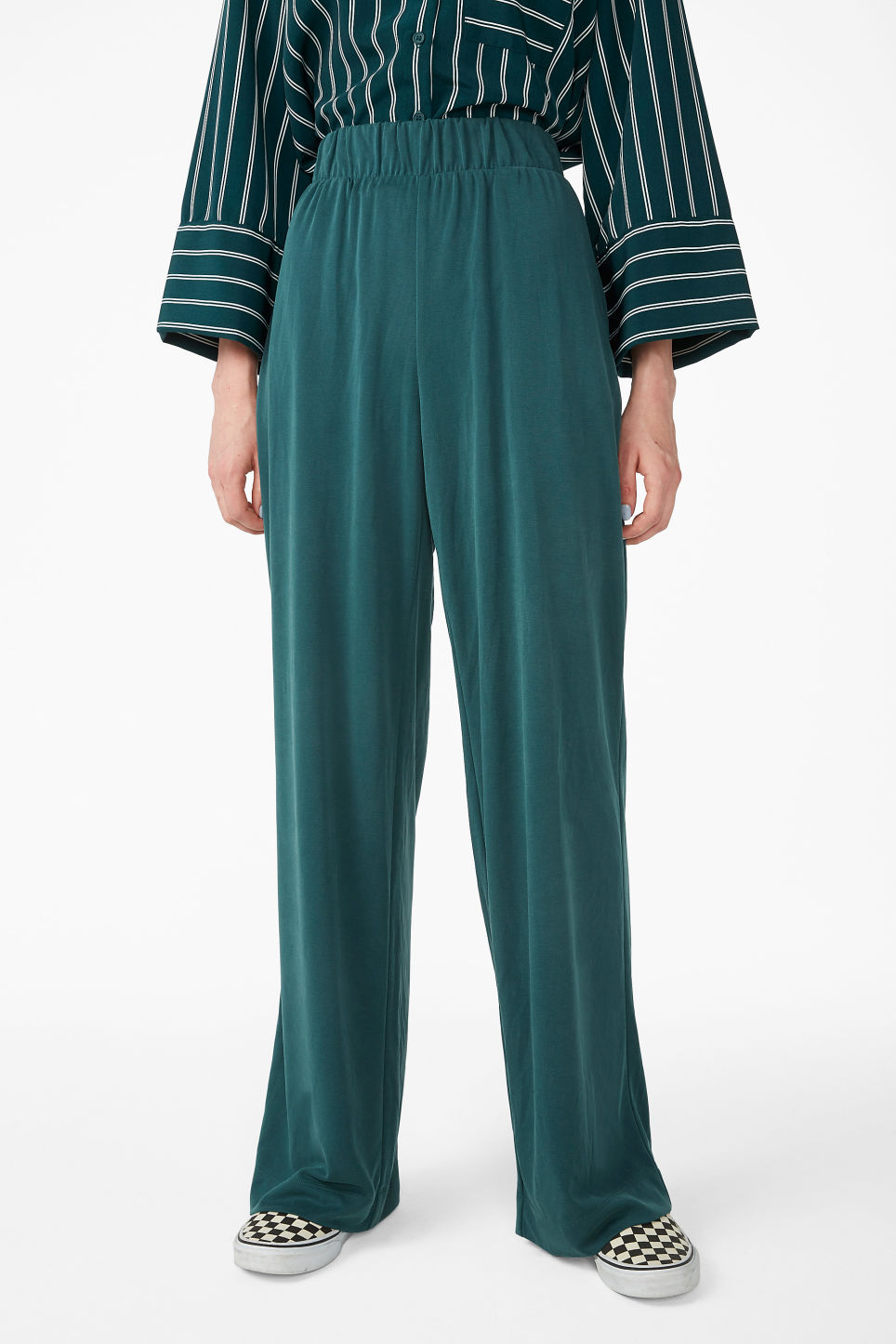 Model side image of Monki super-soft flowy trousers in green