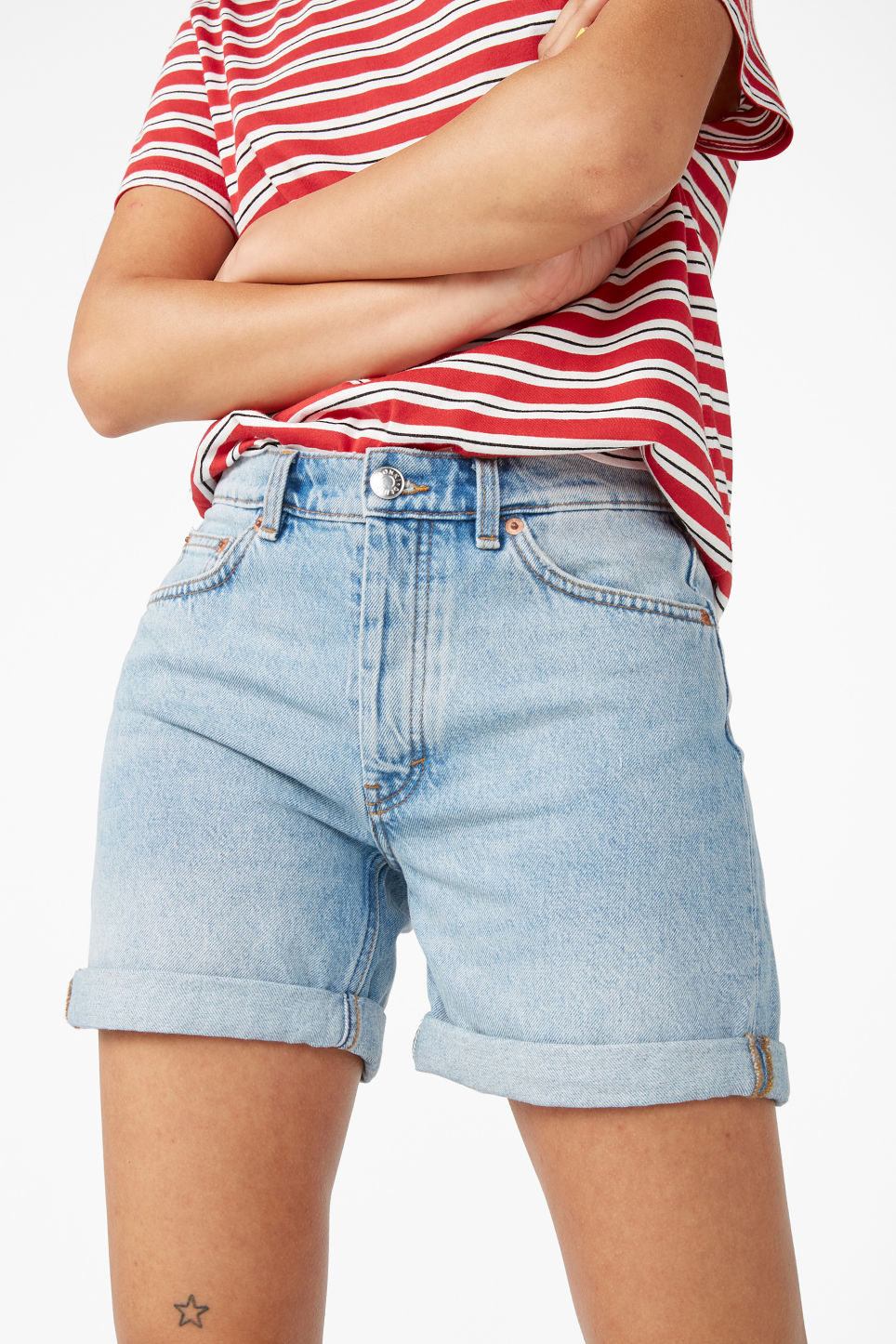 Model side image of Monki high waisted denim shorts in blue
