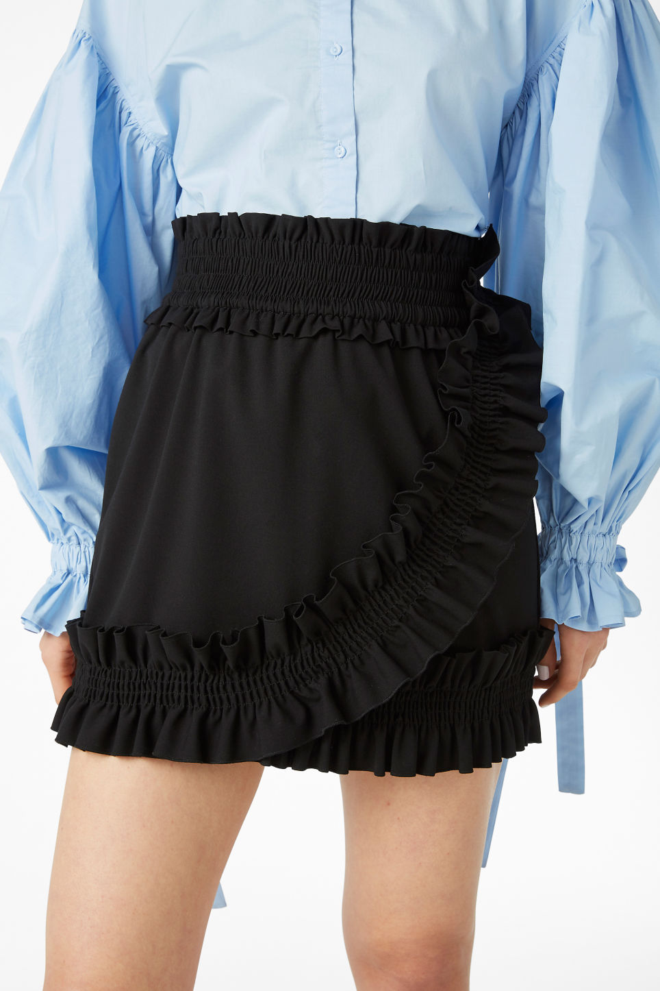 Model side image of Monki ruffled mini skirt in black