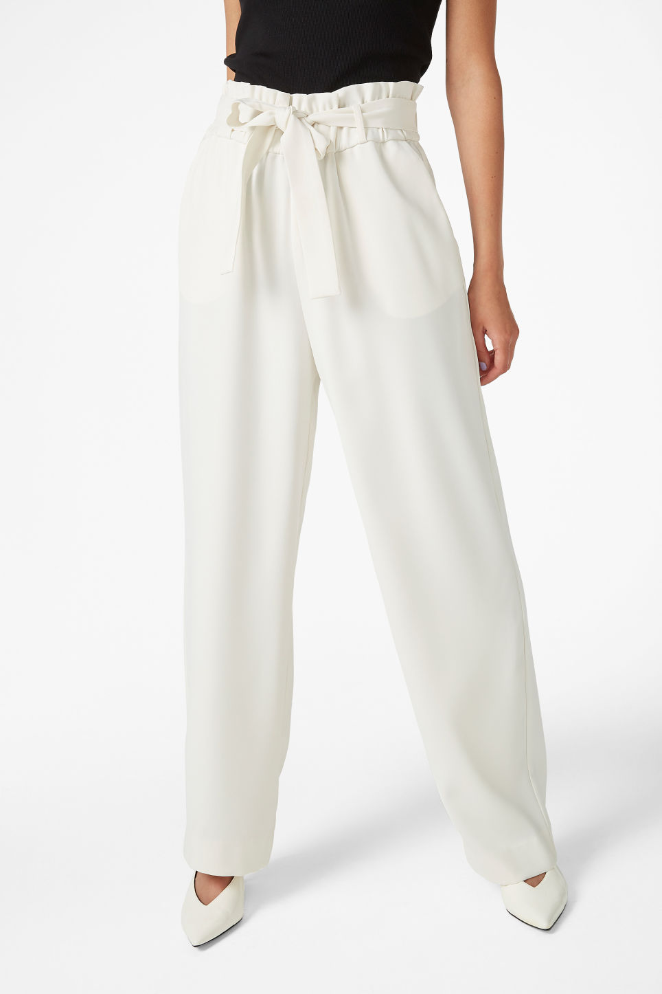 Model side image of Monki flowy trousers in white