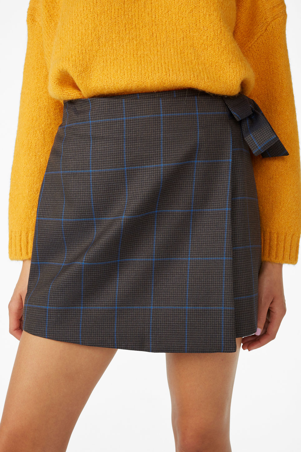 Model side image of Monki mini wrap skirt in grey