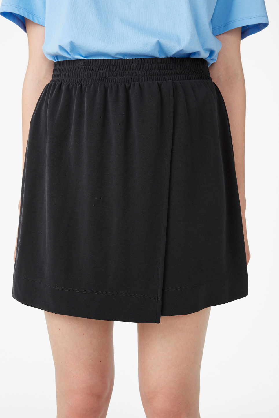 Model side image of Monki super-soft micro wrap skirt in black