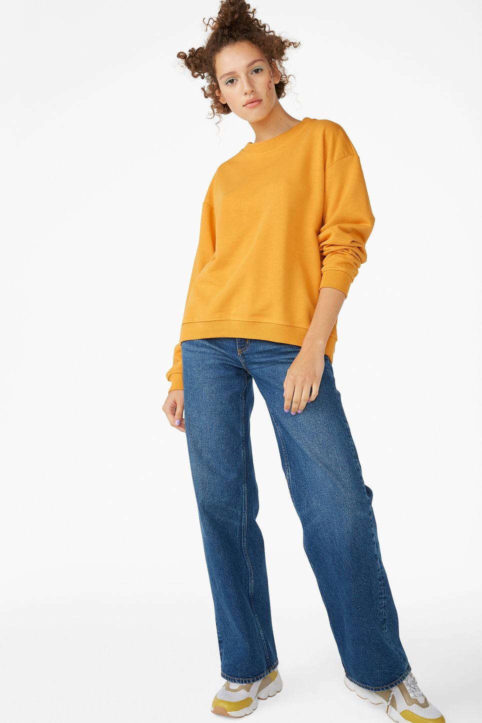 Model side image of Monki loose-fit sweater in yellow