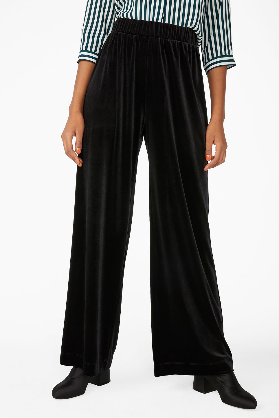 Model side image of Monki flowy velvet trousers in black
