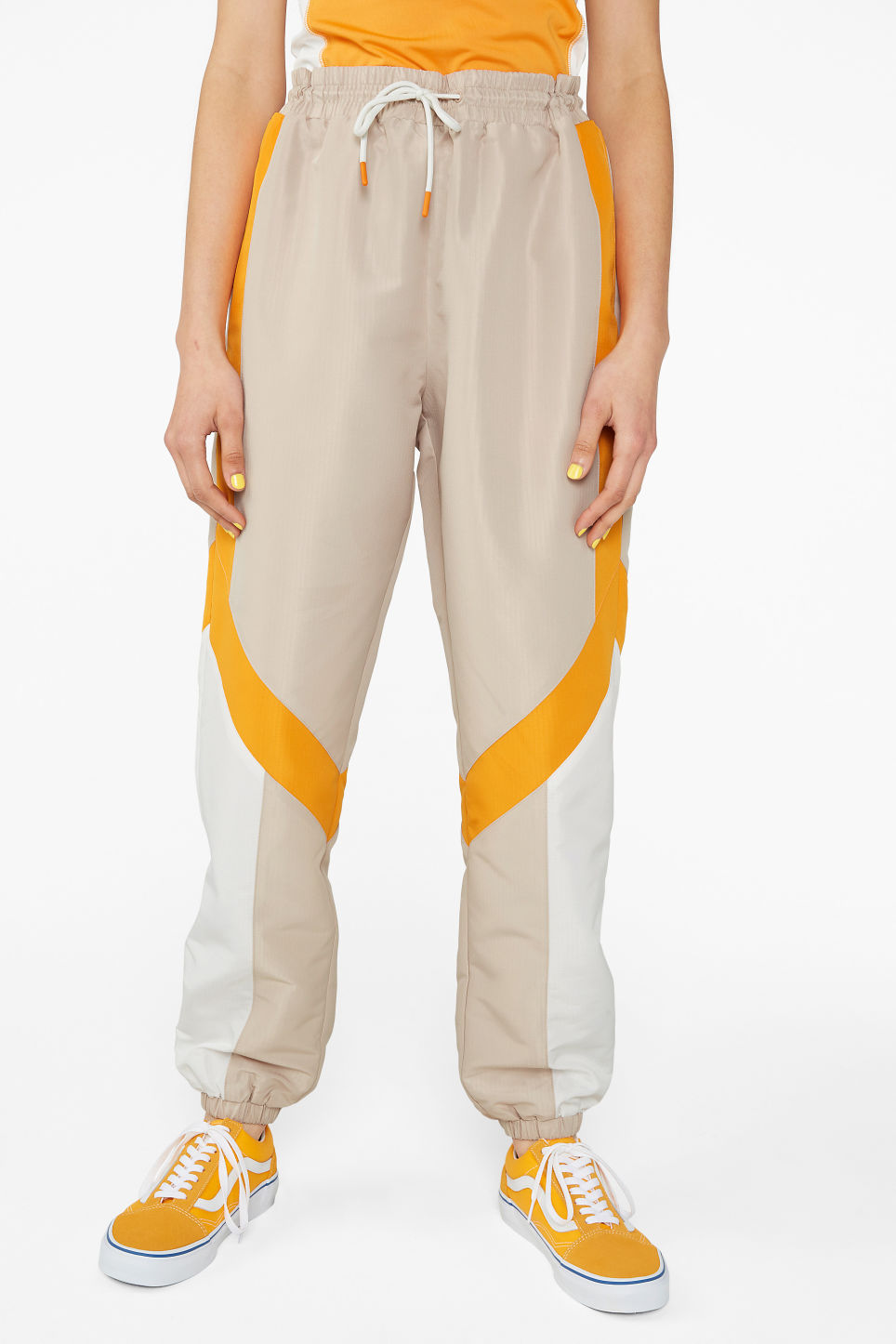 Model side image of Monki track suit pants in beige
