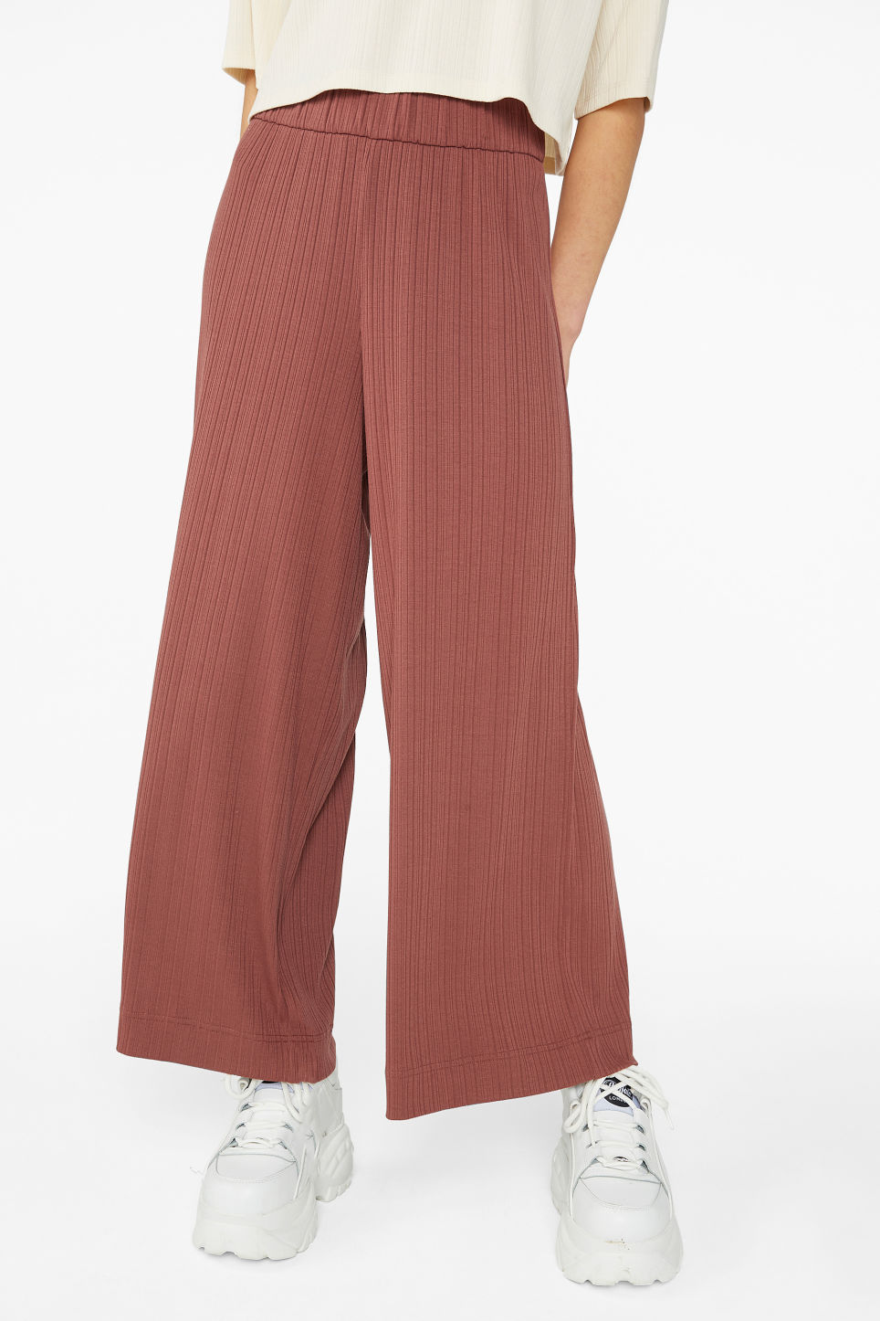 Model side image of Monki wide ribbed trousers in orange