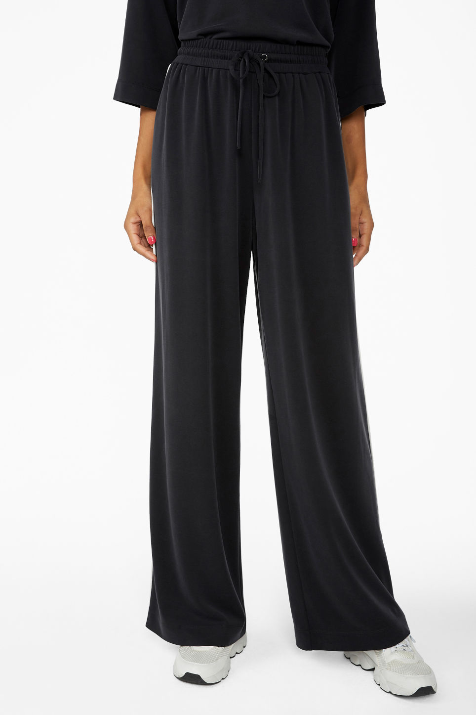 Model side image of Monki super-soft trousers with contrast piping in black