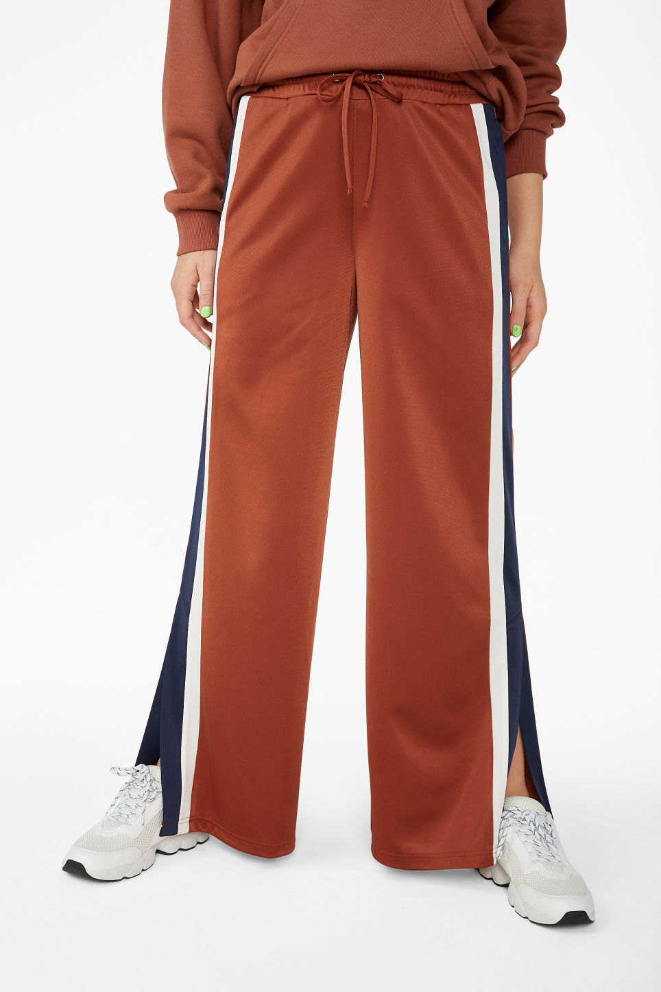 Model side image of Monki track pants in orange