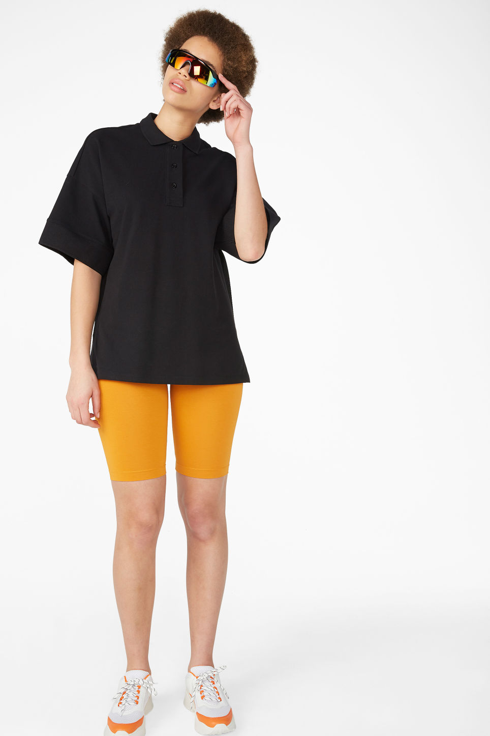 Model side image of Monki oversized polo top in black