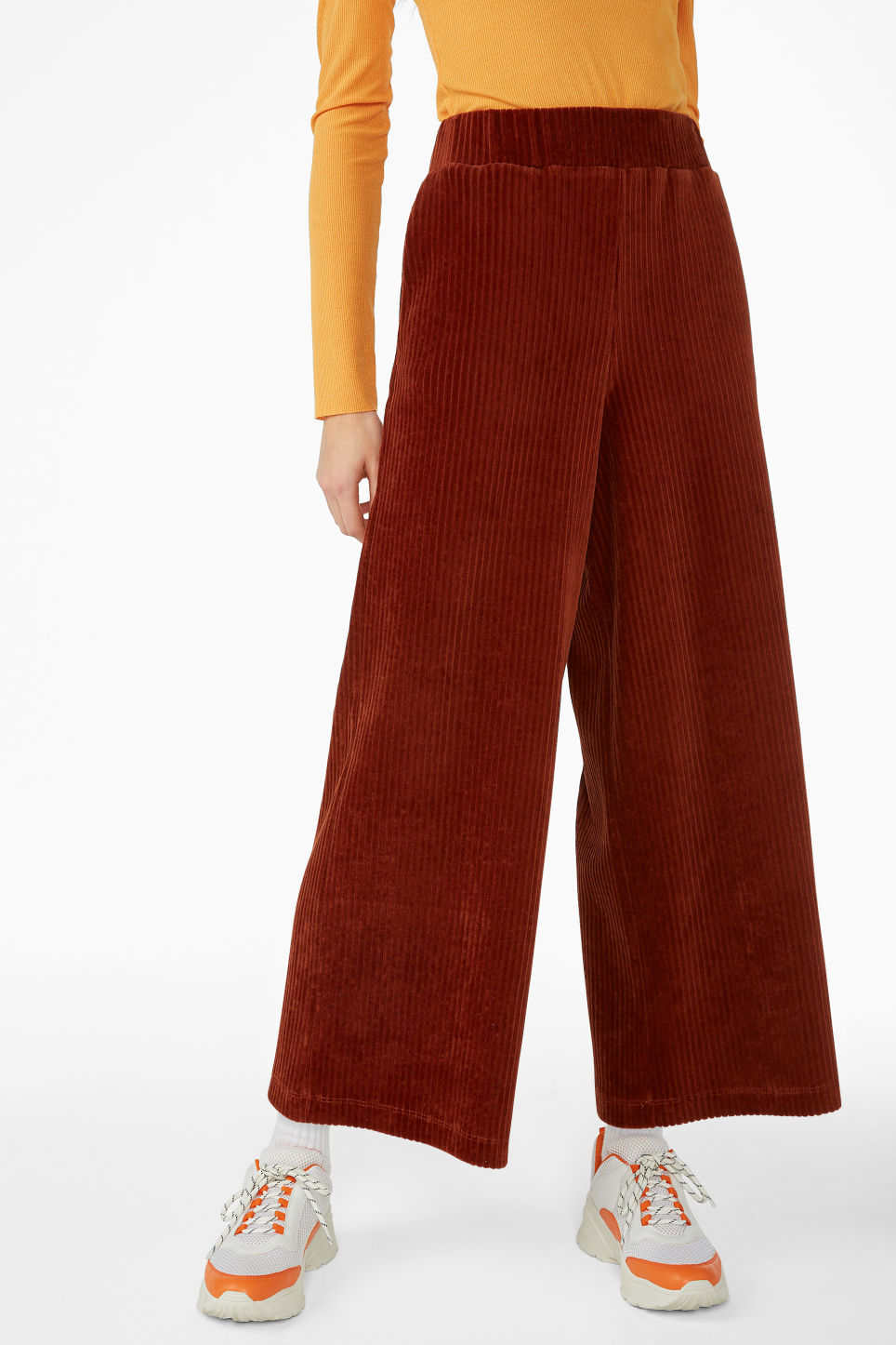Model side image of Monki cropped ribbed velour trousers in orange